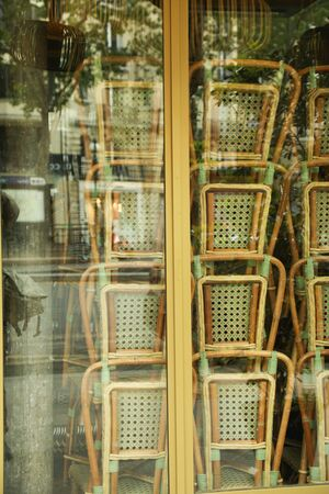 Rattan chairs stacked outside a bistro France Stok Fotoğraf