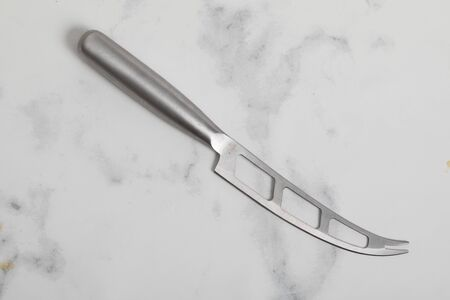 Stainless steel cheese knife on a white marble background. Steel kitchenware 版權商用圖片