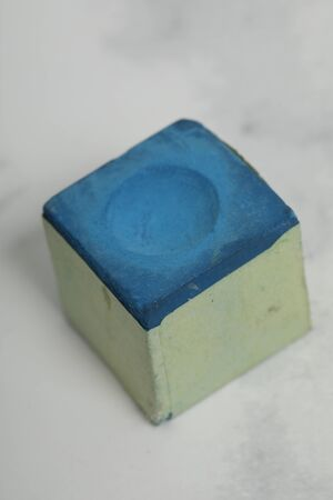 blue chalk cube for snooker game, recreation equipment on white marble