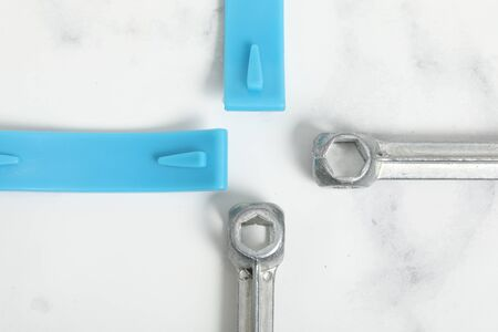 bicycle tire reapair tools on white marble background. Blue and chrome item.