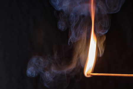 Macro fire burning on matchstick. Studio shot isolated on black background.