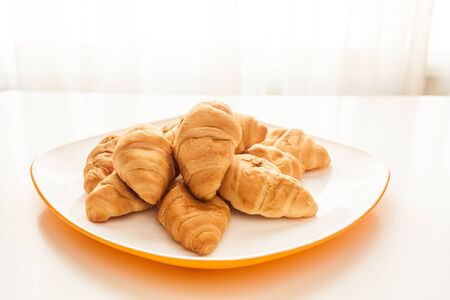 Mini croissants in a plate on a table with natural light Stock Photo