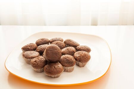 Tasty muffins in the plate on the table near to window with natural sun light