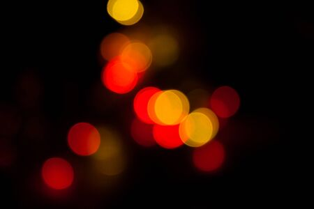 Blurred spots of yellow and red lights bokeh for abstract color background