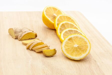 Sliced ginger and lemon slices on wooden cutting board