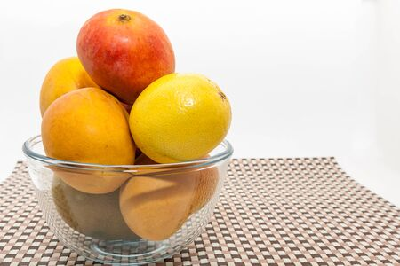 Ripe yellow and red mango fruits in glass bowl on brown check mat