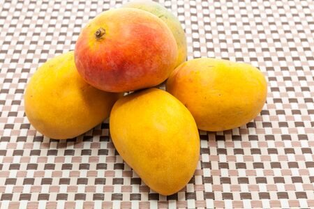 Ripe yellow and red colored mango fruits on brown check mat background