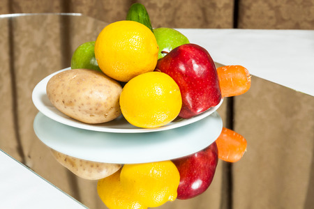 A plate of fruits and vegetables on a table with mirror reflection