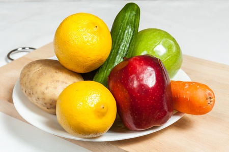 A plate of fruits and vegetables on a cutting board Stock Photo