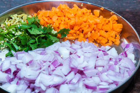 Side view of a plate of cut pieces of onion, carrot, coriander leaves, ginger