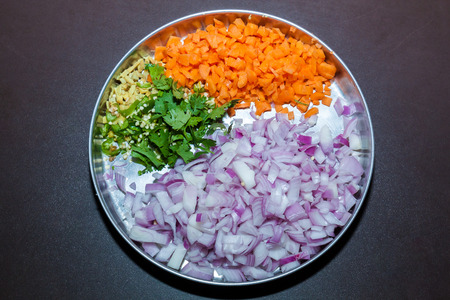 Top view of a plate of cut pieces of onion, carrot, coriander leaves, ginger