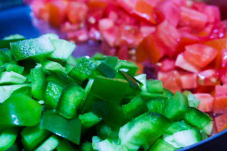 Close up sliced green capsicum in a plate with sliced red tomato out of focus