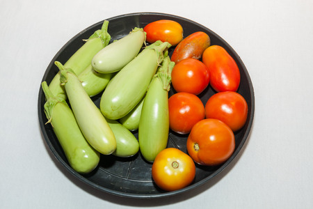 Fresh red tomatoes and egg plants in a balck plastic plate Stock Photo