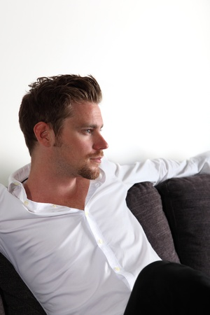 looking away from camera: Man sitting in sofa looking away from camera. White background. Stock Photo