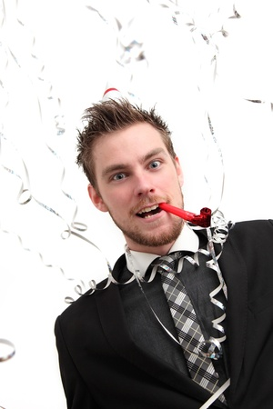 Crazy Party guy with hat and party blower. Wearing a suit. White background. Stock Photo - 17341206