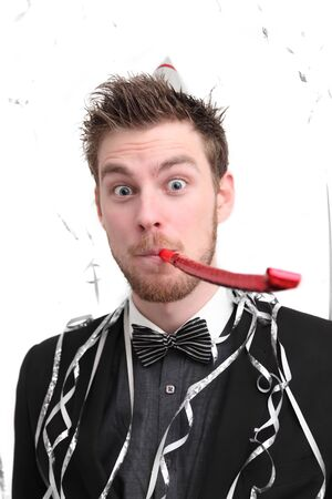 Party guy with hat and party blower. Wearing a suit. White background. Stock Photo - 17341144