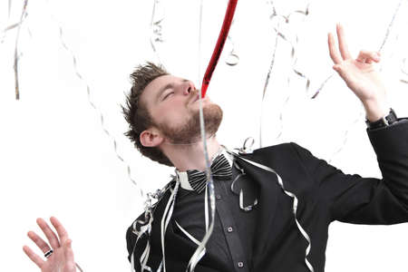Party guy with  party blower. Wearing a suit and bowtie. White background. photo
