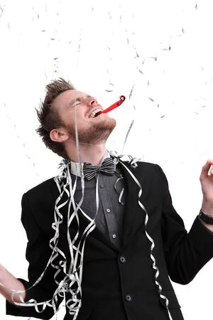 Party guy with hat and party blower. Wearing a suit. White background. Stock Photo