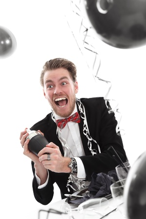 Crazy looking party guy with cocktail shaker. Wearing a black suit and bowtie. White background. Stock Photo