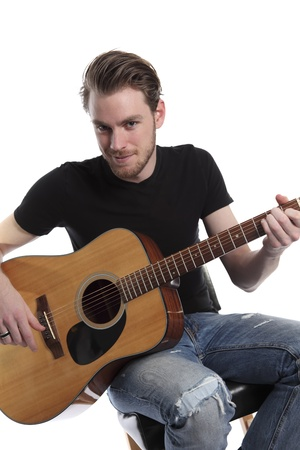 Young adult singer songwriter with an acoustic guitar sitting down. Wearing a black t-shirt with torn jeans. White background. Stock Photo - 17329625
