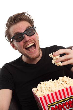 Happy man in 3-D glasses holding a popcorn bowl. Wearing a black t-shirt. White background. photo