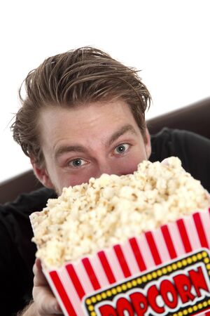 Man looking up from a popcorn bowl. Wearing a black t-shirt. White background. photo