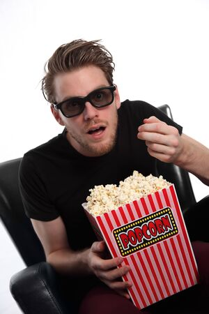Amazed man in 3D-glasses with a popcorn bucket looking into camera. Wearing a black t-shirt. White background.