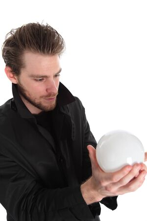 Man holding a glass ball, wearing a black coat. White background. photo