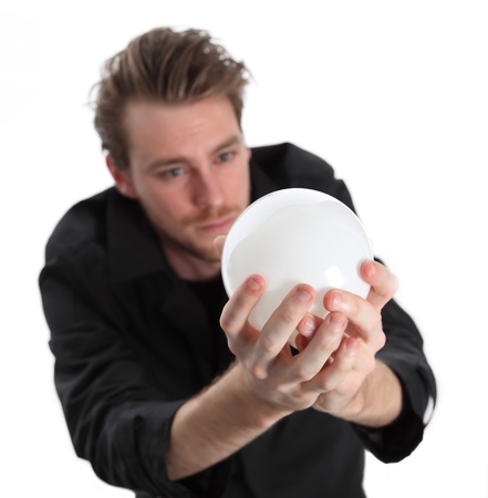 Man looking into a glass ball, wearing a black coat. White background. photo