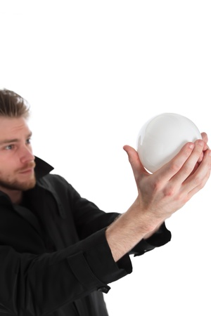 Man looking up into a glass ball, wearing a black coat. White background. photo