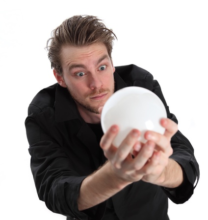 Man looking into a glass ball, wearing a black coat. White background. Stock Photo