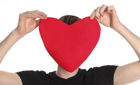 Who is your sweet heart, man holding a big soft heart in front of face. White background.