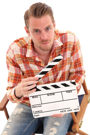 Man holding a film slate sitting down. White background.