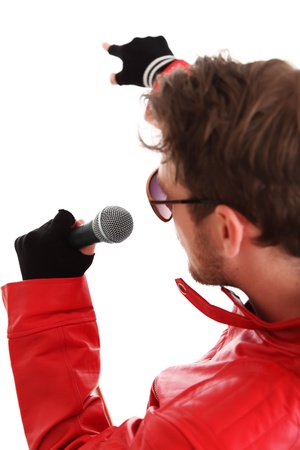 Rock Star pointing. Holding a microphone. Wearing a red leather jacket. White background.