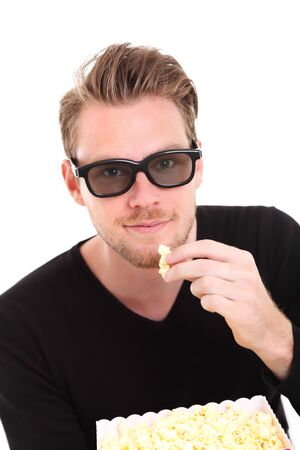 Man in 3D-glasses with a popcorn bucket, sitting down. White background. Stock Photo - 17360480