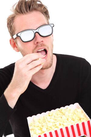 Man in 3D-glasses with a popcorn bucket, sitting down  White background  photo