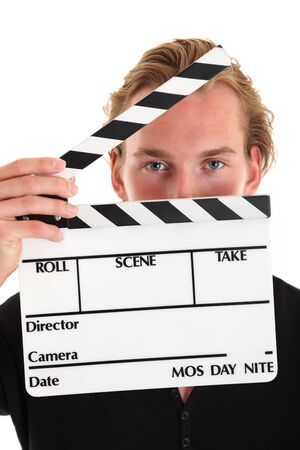 Man holding a film slate. Wearing a black shirt. White background.