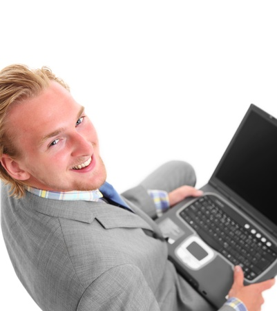 Young businessman working on laptop. Wearing a grey suit and a blue tie. White background. Stock Photo - 17369331