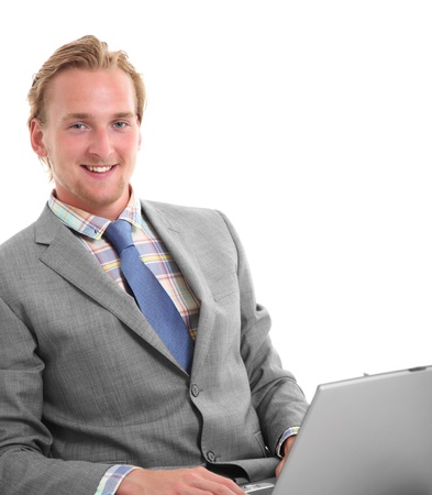Smiling young businessman holding a computer. Wearing a grey suit with a blue tie. White background. Stock Photo - 17369309
