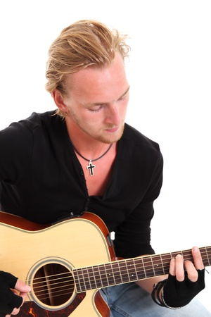 fingerless gloves: Young singer-songwriter sitting down with an acoustic guitar. Wearing fingerless gloves and a black shirt. White background.