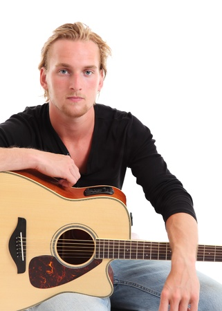 Young singer-songwriter sitting down with an acoustic guitar. White background. photo