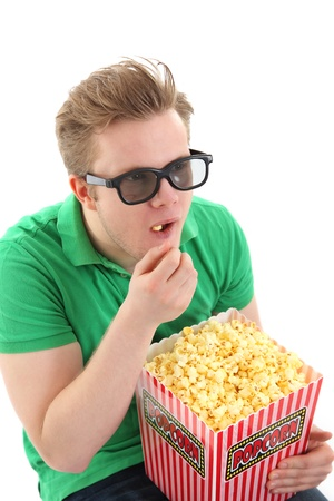 Amazed man in 3D glasses with popcorn bucket. Wearing a green shirt. White background.