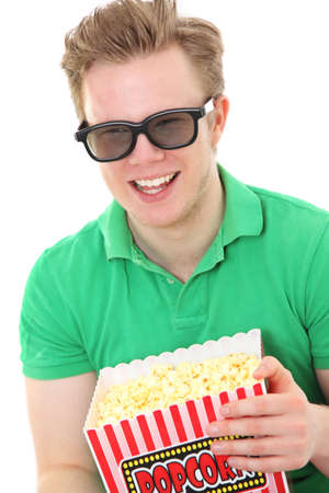 Happy man in 3D glasses holding a popcorn bucket. Wearing a green shirt. White background. photo