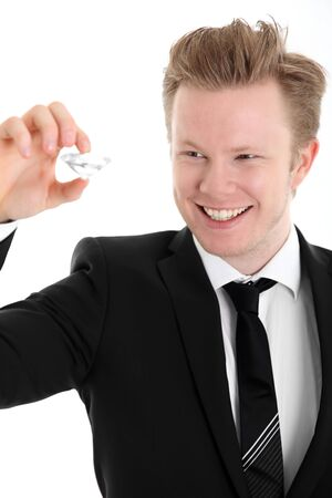 Found the one. Young man in suit and tie holding a large diamond. White background.