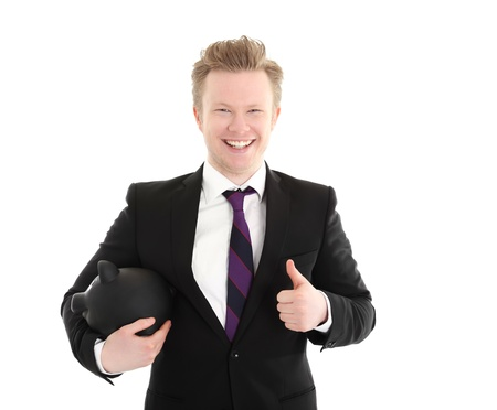 Businessman holding a piggybank. Wearing a black suit with a purple tie. White background. Stock Photo