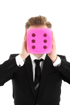 Businessman holding a large dice in front of his face. Wearing a black suit and black tie. White background. photo