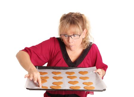 newly baked: I�ll just take one. Female baker trying the newly baked cookies. White background.
