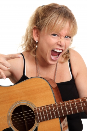 Screaming female holding an acoustiv guitar doing the heavy metal sign. White background. Stock Photo - 17417026
