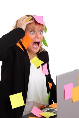 Crazy businesswoman with post-it all over and lap top. White background. Stock Photo