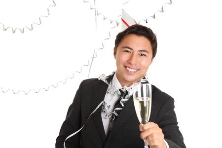 Cheers! Young man wearing a suit, tie and party hat, holding a champagne glass. White background. photo